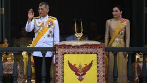 King Maha Vajiralongkorn and Queen Suthida wave to well-wishers