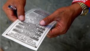 A sample ballot being held in hands belonging to a Duterte supporter, wearing Duterte wristbands, in Davao city on 9 May
