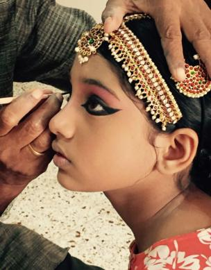 A young girl has eyeliner applied