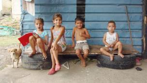 Cuatro niños frente a caseta de zinc