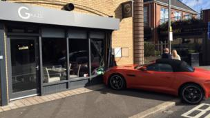 A Jaguar convertible car crashed into the window of a restaurant in east Belfast after being involved in a collision. The owner of the car told the BBC he was shaken but unhurt.