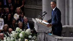 Former US President Barack Obama speaks at the memorial service, from a lectern flanked by white flowers