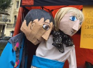 Two puppets lean on each other