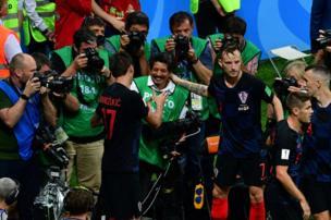 مهاجم فريق كروايتا ماريو ماندزوكيتش يصافح مصور وكالة الأنباء الفرنسية يوري كورتيز بعد وقوعه وسط اللاعبين المحتفلين بتسجيل هدفهم الثاني في مبارات نصف النهائي أمام إنجلترا