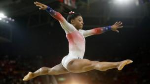 Simone Biles en un salto con las piernas abiertas a los lados.