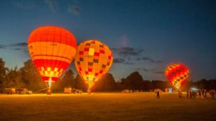 The balloon festival, a local charity event, at Cholsey. As a festival finale three hot air balloons glow together in the twilight.