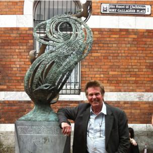 Irish musician Joe Brown poses beside Geraldine Creedon's sculpture at Rory Gallagher place in his hometown of Cork