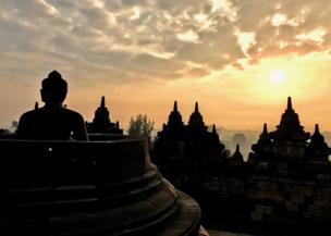 Es un atardecer donde sobresalen las sombras de un templo que se caracteriza por sus puntas y una enorme buda que sobre sale en la imagen.