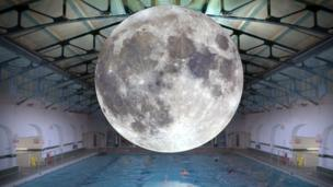 Moon balloon superimposed above a swimming pool