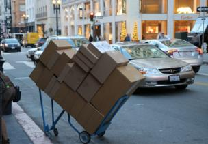 A large pile of boxes neatly stacked on a trolley on a busy street
