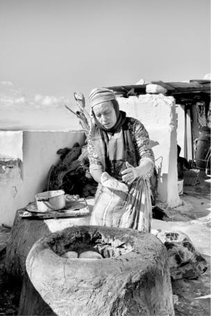 A woman prepares flatbread in an outdoor kiln