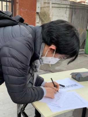 11 febrero 2020. Michael llenando sus datos y grado de temperatura en un registro fuera de un compound, en Pekín.