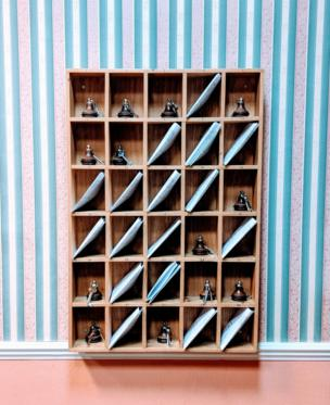 Shelf unit containing keys in front of striped wallpaper