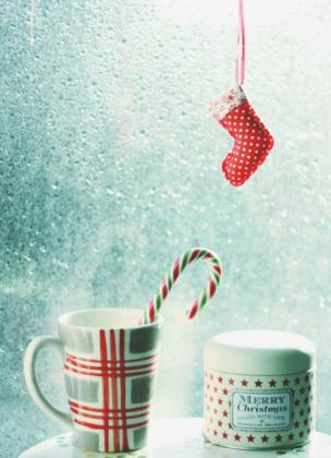 A small stocking hanging next to some festive mugs