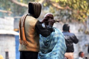 Hombre afeitando a otro en la calle
