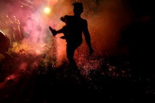 رجل من جزيرة بالي يلقي بقذيفة مشتعلة من جوز الهند.