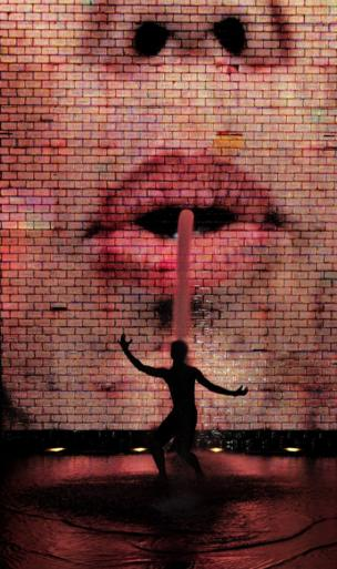 A person dances in a fountain in front of a large LCD screen of a face