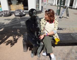 Señora conversando con una escultura de la escritora danesa Lise Nørgaard.