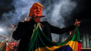 A supporter of far-right lawmaker and presidential candidate for the Social Liberal Party (PSL), Jair Bolsonaro, wears a mask of US President Donald Trump