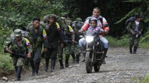 Farc rebels march towards a transition zone as a local resident rides past with a child on a motorbike in Cauca province, in Colombia, on 31 January 2017