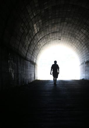 A figure makes its way through a tunnel