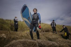 A woman holds a surfboard whilst an Orthodox Jewish family gather behind her
