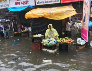 A vegetable seller sits at his stall, amid a flood left by the heavy rains in Mumbai.