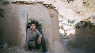 Мальчик у низкого входа в дом