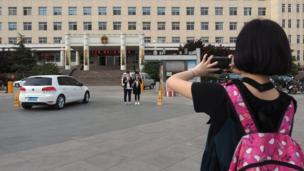 游客在河北雄县政府办公大楼前留影。