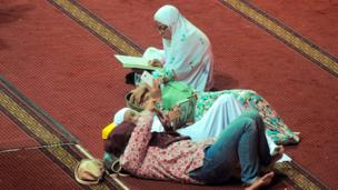 امرأة تقرأ القرآن في مسجد في جاكرتا