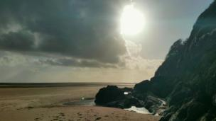 The sun peeping around the clouds on on Llansteffan beach on the Carmarthenshire coast