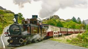 Full steam ahead: The Blaenau Ffestiniog narrow gauge train steams over the level crossing at Tanygrisiau on its journey to Porthmadog