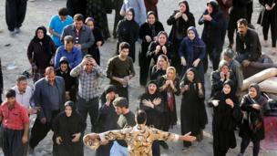 Iranian victims of the earthquake mourn and try to get closer to the body of a relative