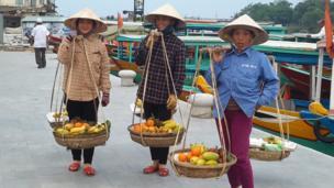 Three women hold fruit baskets