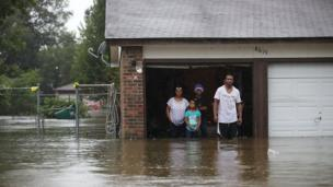 A family waiting to be rescued from their flooded home.