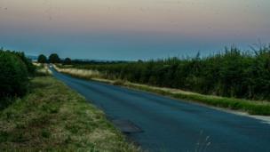The Earth's shadow appears as a dark band across the sky near the horizon as the sun sets near Oxford Airport.