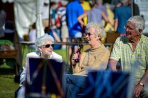 Tres personas de la tercera edad conversan durante una feria estival en Inglaterra