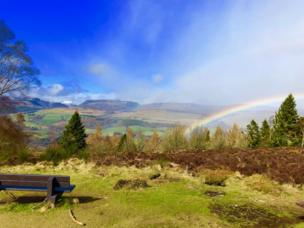 Mountains with snow in the distance, valleys of greenery and a rainbow shines through the clouds
