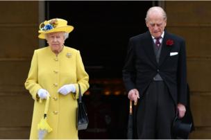 Queen Elizabeth II and the Duke of Edinburgh observing a minute's silence at the start of a garden party at Buckingham Palace in London.