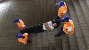 """Rescuers carry a mock victim down the stairs of the Light Railway Transit, LRT, station during a Metro-wide earthquake drill to test various government agencies"""" response in Manila, Philippines on Wednesday, June 22, 2016."""