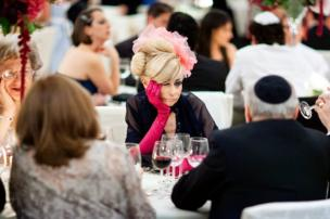 A woman attending a wedding. wearing in a fascinator and pink gloves she holds her face in disappointment