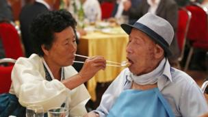 "South Korea""s Ahn Jong-ho (R), 100, receives food from his 70-year-old daughter Ahn Jung-soon"