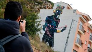 A man takes a photo of a street art mural on the facade of a house in Fanzara near Castellon de la Plana
