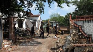 Police officers walk at the residence of Panama's former dictator Manuel Antonio Noriega, currently imprisoned in Panama, Panama City, as it is being demolished on January 9, 2014 following a decision by the Health Ministry for considering it a breeding site of the Aedes mosquito that transmits dengue.