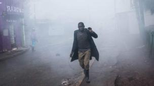 One man wey dey run away from teargas inside Kibera, wey be one of di poorer areas for Kenya capital Nairobi.
