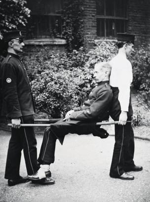Two men carry another on a stretcher