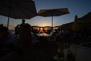 A pair of sunglasses are held up to the sun as it sets over a beach bar