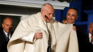 Pope Francis greets the faithful at the Apostolic Nunciature to Colombia in Bogota wearing a ruana.