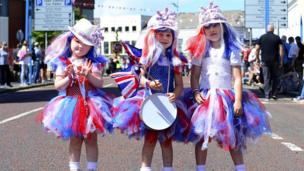 Three girls are dressed in homemade union jack outfits, tutus and wigs