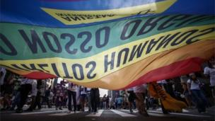 People attending Sao Paulo's Gay Pride parade carry a rainbow flag